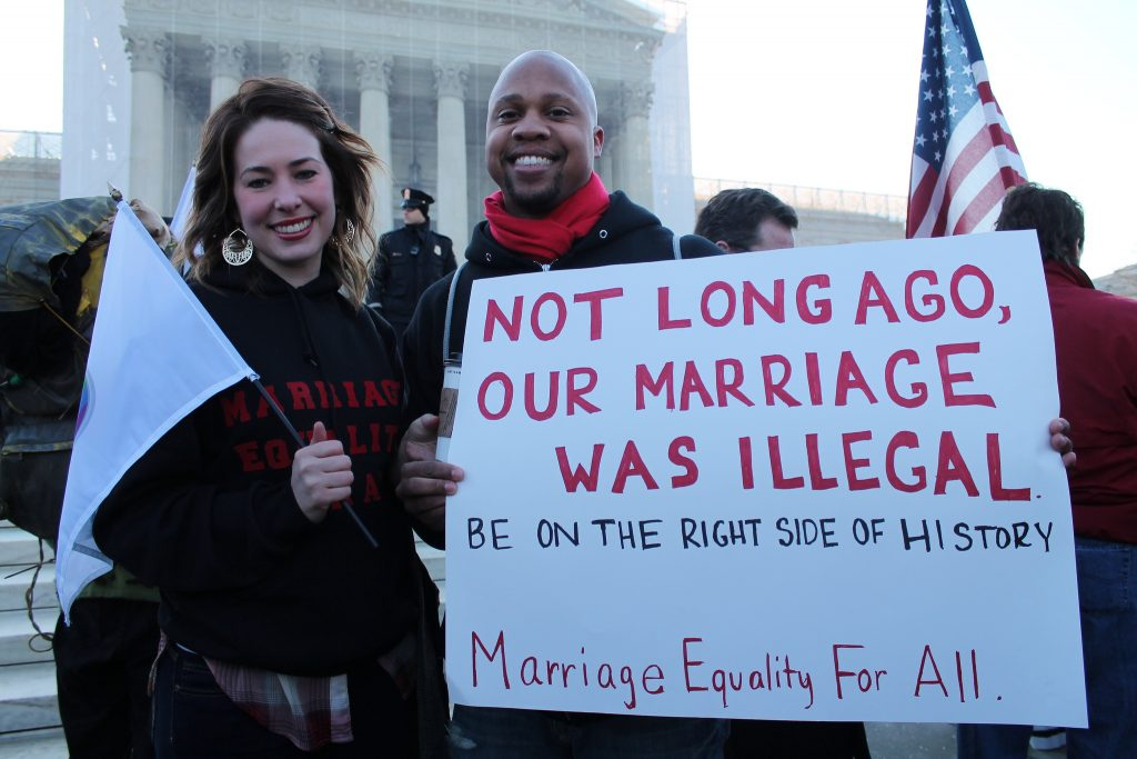 "White woman and black man hold placard reading ""Not long ago our marriage was illegal: be on the right side of history"""