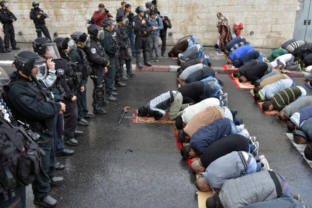 Palestinians pray as they are prevented from entering mosque xompound