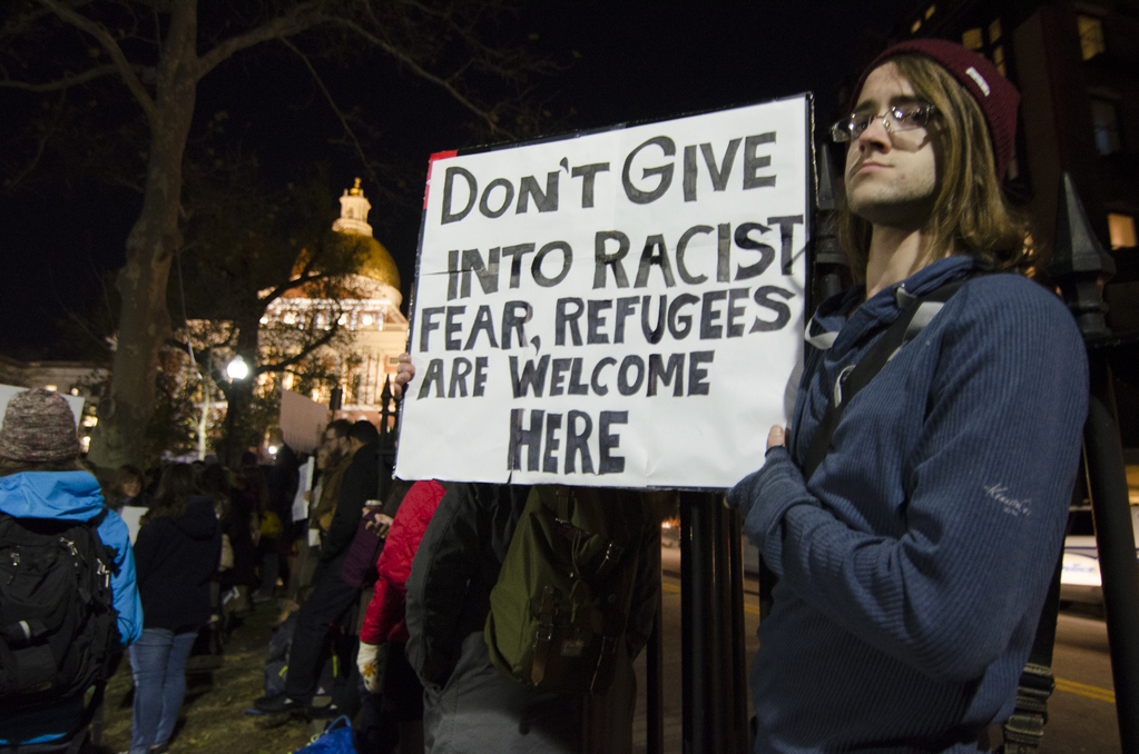 "Protester holds placard reading ""don't give in to racist fear, refugees are welcome here"""