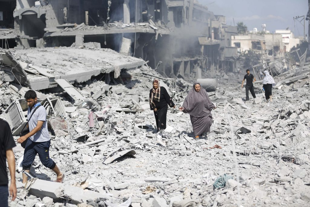 Women walk through rubble after bombing