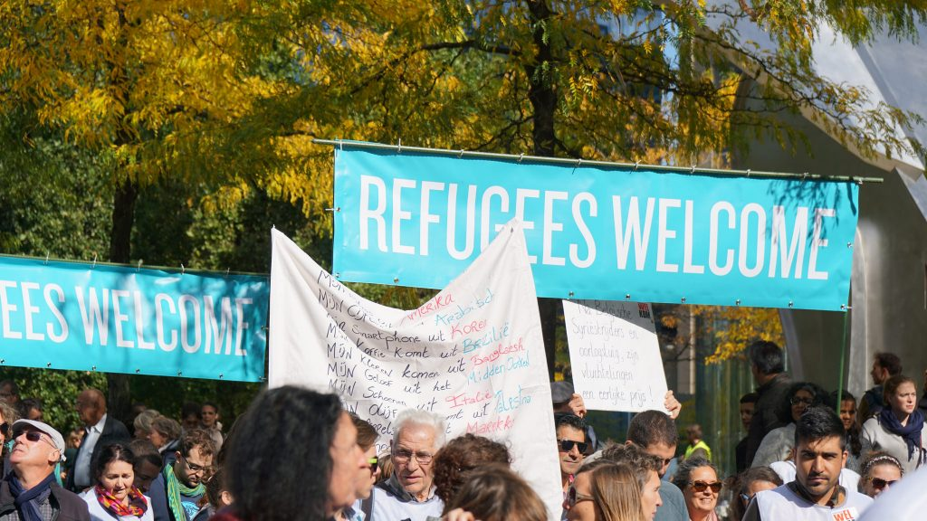 Banners read Refugees Welcome