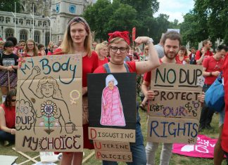 Pro choice demonstrators with placard showing woman in handmaid dress