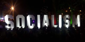A sign made up of large illuminated wooden letters ln the dark that says 'socialism'