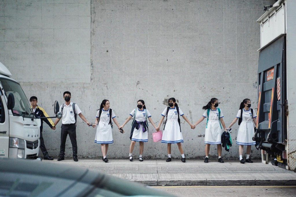 Seven children, five of them in black smog masks and white school uniforms, stand holding hands forming a chain in front of a grey wall.