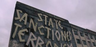 A large brown and grey banner hanging on a concrete building, with the hand-painted text 'State Sanctioned Terrorism'