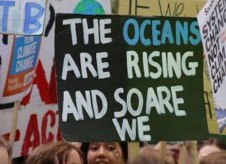 A handpainted banner reading 'The oceans are rising and so are we'