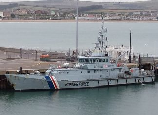 An aerial image of a ship of the UK Border Force docked in a port.
