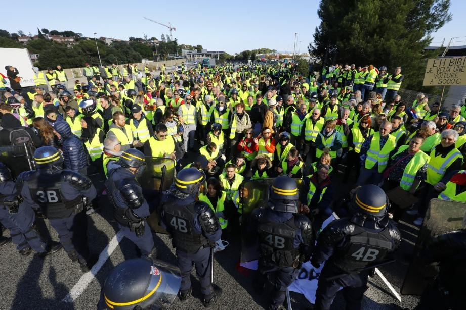 A group of gilet jaunes (yellow vest) protesters facing up to a line of riot police