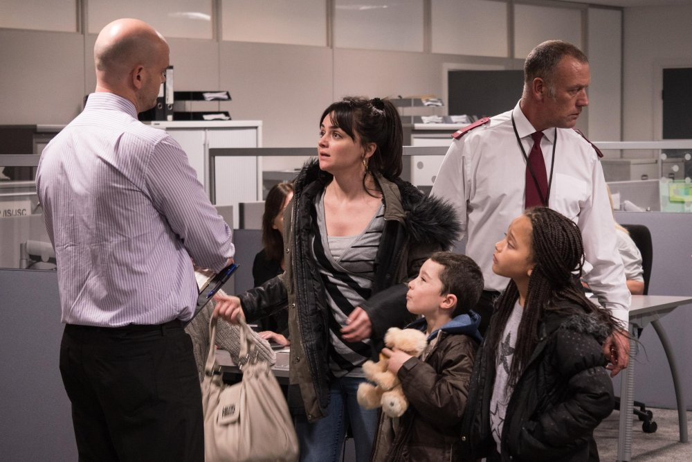 Actor Hayley Squires and two child actors surrounded by two men dressed as security guards in a scene of the film 'I, Daniel Blake'