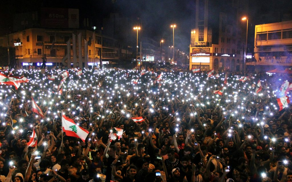 Thousands of people gathered on a street at night, waving Lebanese flags and shining phone torches.