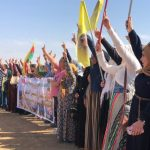 A group of people raise flags and show peace signs on a demonstration in Rojava, north-east Syria.