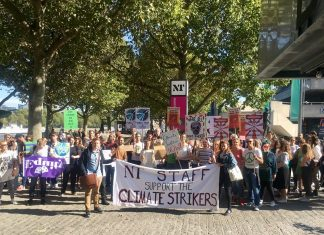 A group of artworkers stand with a banner outdoors on the Southbank in London