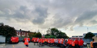 Postal workers in orange work jackets stand in a parking lot, with flyers of the Communication Workers' Union in their hands.