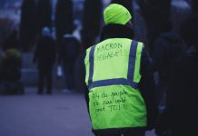 A person on the street wearing a yellow vest, photographed from the back, with a handwritten message on the vest in French reading 'Macron resign, 3/4 of people didn't vote for you'