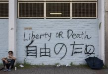 A graffiti reading 'liberty or death' on a white wall, with a person sitting on the floor on the left hand side.