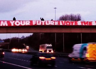 "Giant banner across bridge reads ""reclaim your future. Vote the Tories out"""