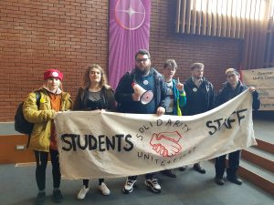 Students with megaphone and banner reading Solidarity: Staff, Students, unite and fight