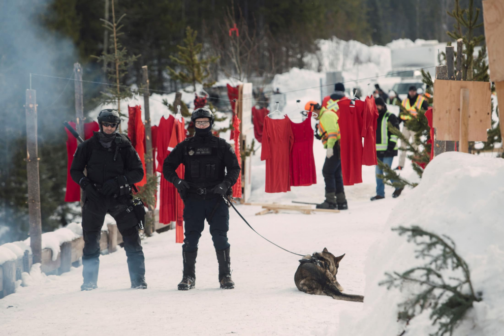 Armed RCMP officers with dogs stand on Unist'ot'en lands, while officers remove red dresses used in the ceremony (background)