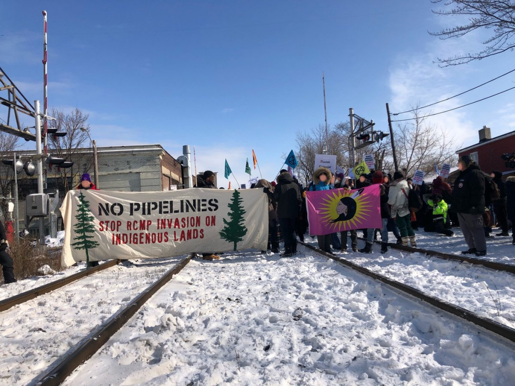 "Indigenous-led rolling blockade in Ontario; banner reads ""NO PIPELINES: Stop RCMP invasion on indigenous lands"""