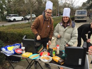 Students in chef hats making pancakes outside