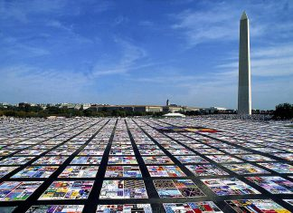 The AIDS Quilt memorial laid out in an open square.
