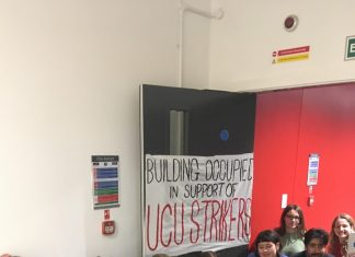 Students sit on the floor in a doorway at University of Manchester underneath a handpainted banner reading 'Building occupied in support of UCU strikers'. Some hold a smaller banner reading 'Equal pay for BME staff'