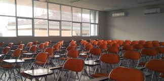 Rows of orange chairs in an empty classroom.