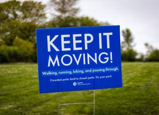 A blue sign in a grassy park that reads 'Keep it moving@