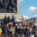 Protesters at a Black Lives Matter demonstration in London, standing around Nelson's Column with banners.