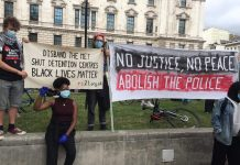 Protesters hold two banners reading 'Disband the Met, Shut detention centres, Black lives matter' and 'No justice, no peace, abolish the police'