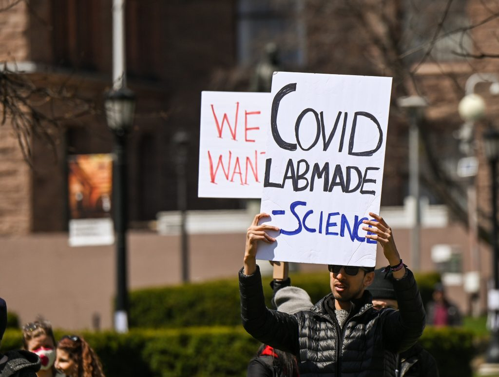 placard read:s Covid: lab-made science