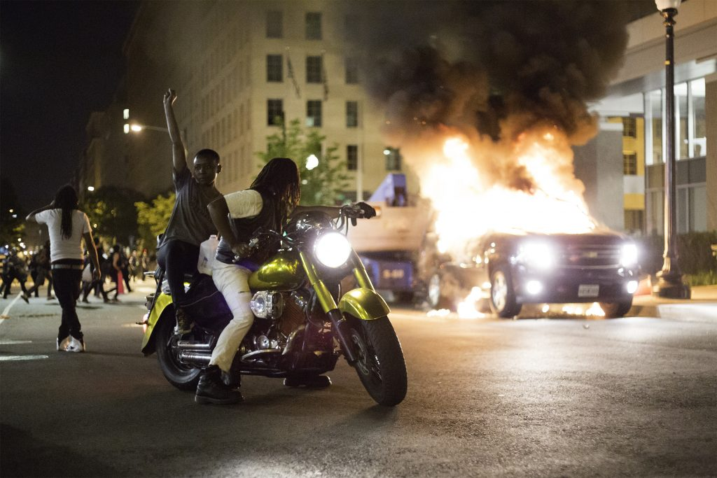 Two Black protesters on a motorbike, one of them raises a fist, in front of a burning car in a dark city street.