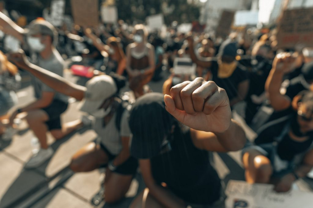 Black protesters kneel and raise a fist at a demonstration.