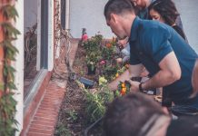 A group of people tending to a small flowerbed under a windowsill.