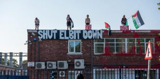 "Four protesters stand on top of Elbit's building with a banner reading ""Shut down Elbit"" and Palestine flags."
