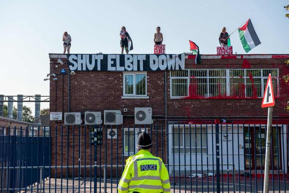 """Four protesters stand on top of Elbit's building with a banner reading """"Shut down Elbit"""" and Palestine flags."""