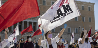 Protestors wave flags at a socially distanced May Day protest in Athens