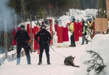 RCMP officers patrol the Unist'ot'en camp with dogs after a raid. In the background, red dresses hang, symbolising Indigenous women missing and murdered under colonial occupation.