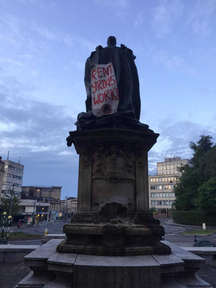 flag hung on a statue, reads: 'rent strikes work'