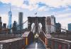 A worker walks along the Brooklyn bridge with the Manhattan skyline on the horizon.