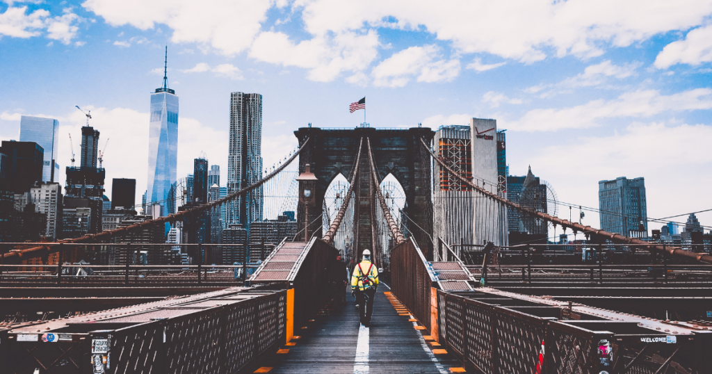 A worker walks along the Brooklyn bridge with the Manhattan skyline on the horizon.