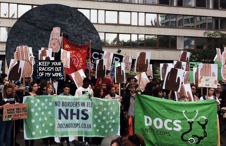 Protesters opposing the enforcement of border control within the NHS. Keywords: Hostile Environment policing Britain