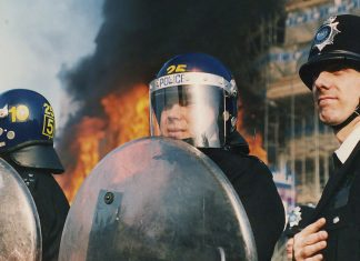Three police officers in riot gear stand infront of a burning building on 31st of March 1990