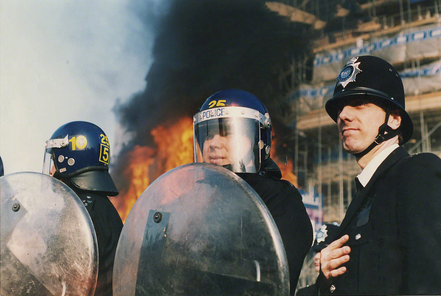 Three police officers in riot gear stand infront of a burning building on 31st of March 1990 Keywords: poll tax violence tactics militant action collective action direct action