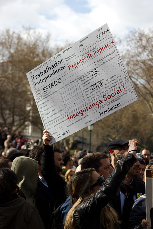 A protester holds up a blown-up version of a piece self-employment paperwork. Keywords: crisis great recession depression organising