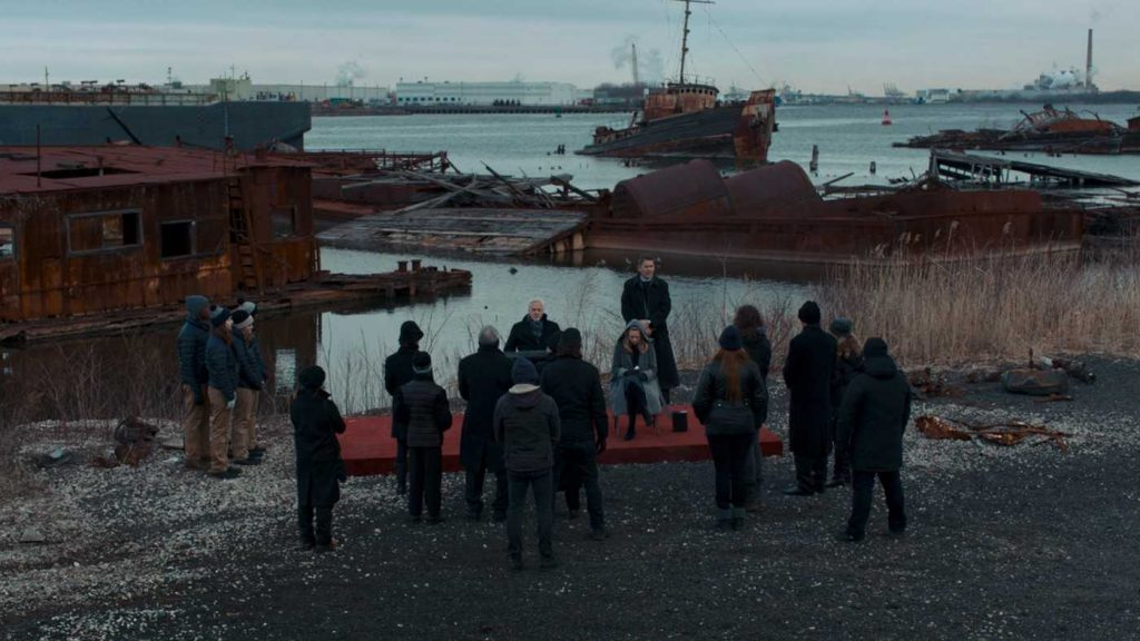Still from funeral scene in First Reformed - a small group gather by a lakseshore littered with rusting boats.