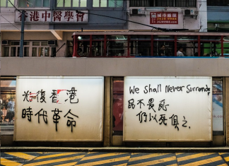 "Image shows graffiti in Hong Kong reading ""We Shall Never Surrender"", both in English and simplified Chinese characters."