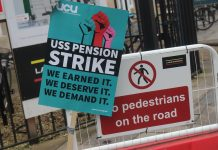 "Image shows a blue placard that reads ""USS pension strike. We Earned It. We deserve it. We demand it."""