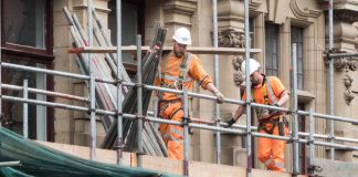 An image of two construction workers on a scaffold. Keywords: Covid coronavirus shut the sites unsafe work safety
