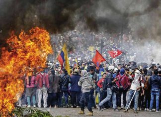 A crowd of protesters standing near to a flame during the mass protest movement in Ecuador in late 2019.